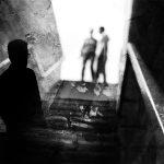 un homme observe en contre-jour un couple à la cime d'un escalier : montage noir et blanc